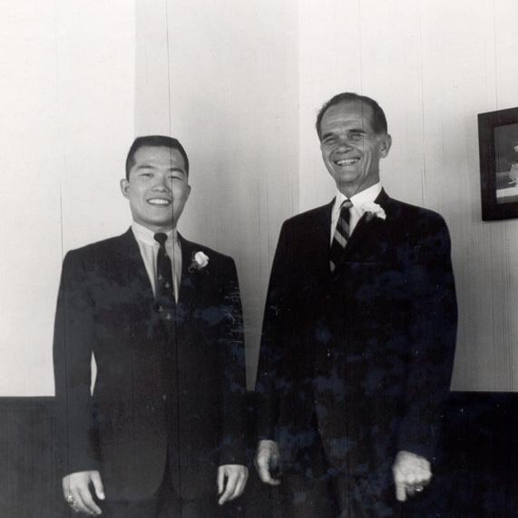 Koji and Bertrand stand next to each other at Koji's wedding